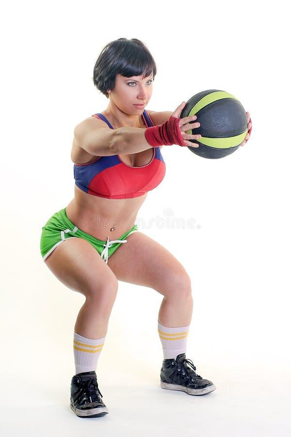 Femme convenable sur un fond blanc tenant une boule de gymnase photo libre de droits