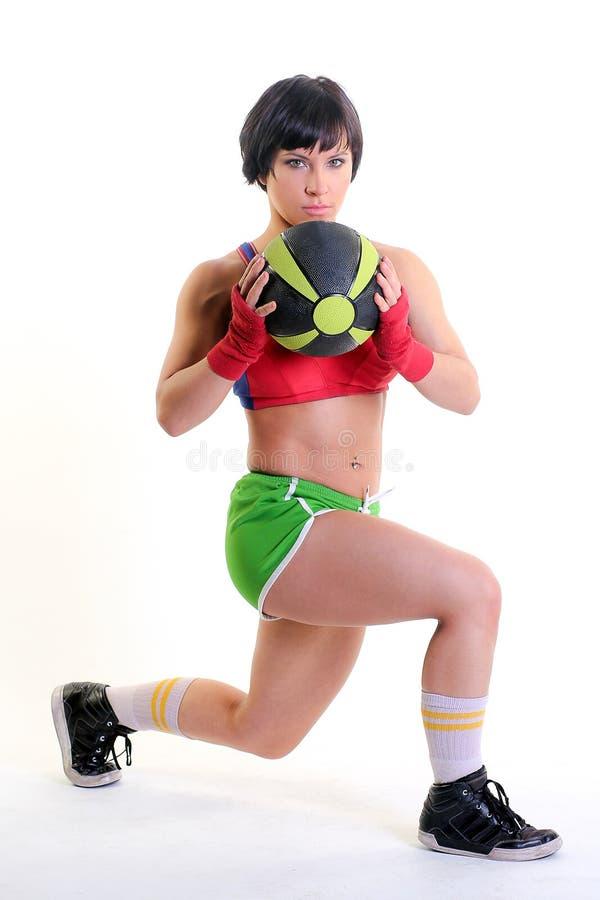 Femme convenable sur un fond blanc tenant une boule de gymnase photos stock