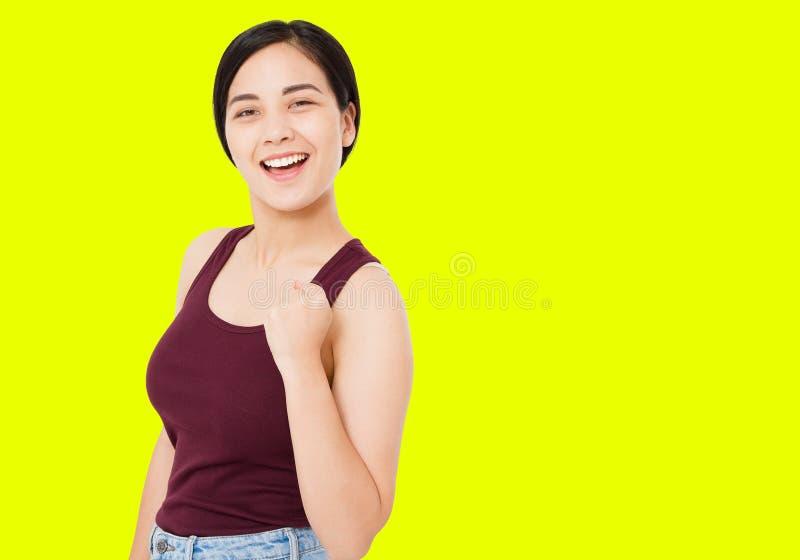Femme coréenne et asiatique réussie d'isolement sur le fond jaune, geste d'exposition de fille des pouces de signe positif de suc images libres de droits
