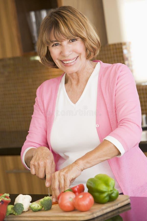 Femme coupant des légumes images stock