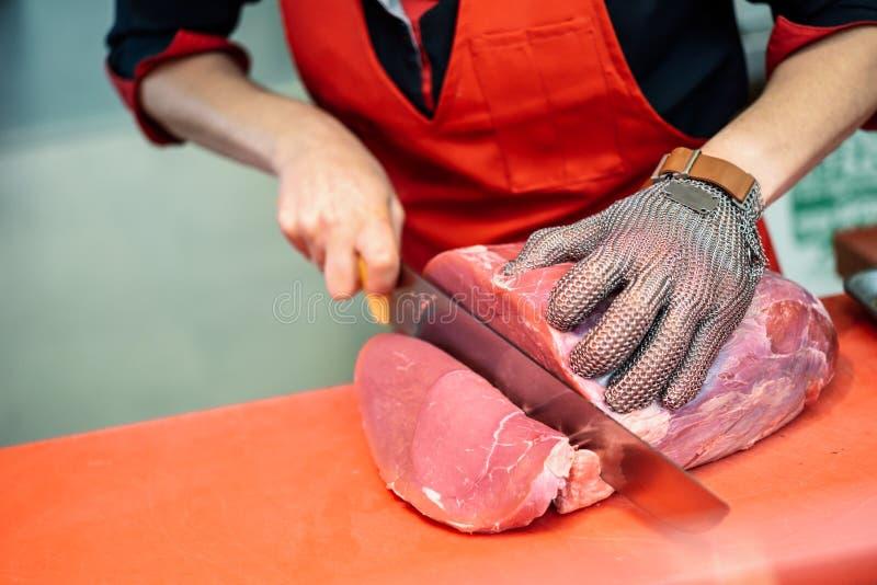 Femme coupant la viande fraîche dans une boucherie avec des mes de sécurité en métal photos stock
