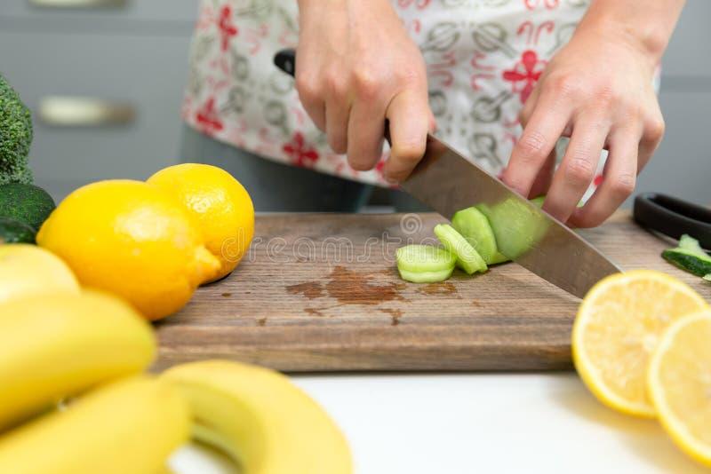 Femme coupant les légumes verts pour le smoothie de detox à la maison Consommation saine, nourriture v?g?tarienne, suivant un r?g images stock
