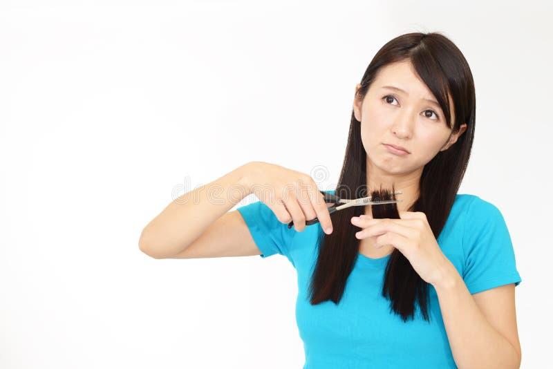 Femme coupant propres cheveux avec des ciseaux image stock