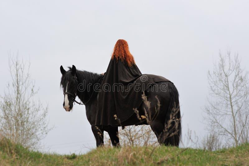 Femme courageuse avec les cheveux rouges dans le manteau noir sur le cheval frison photos libres de droits