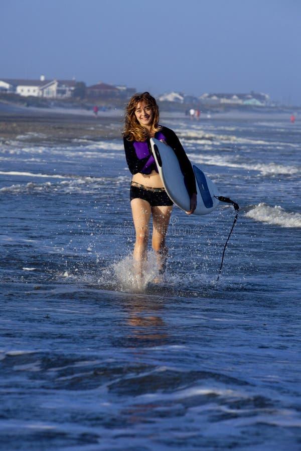 Femme courant avec la planche de surf photographie stock