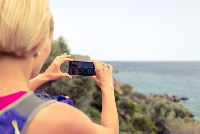 Femme courant avec le sac à dos prenant la photo avec le smartphone images stock
