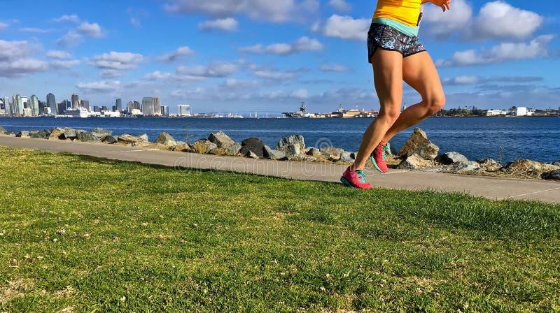 Femme courant le long du bord de mer urbain, San Diego, la Californie, Etats-Unis photo libre de droits