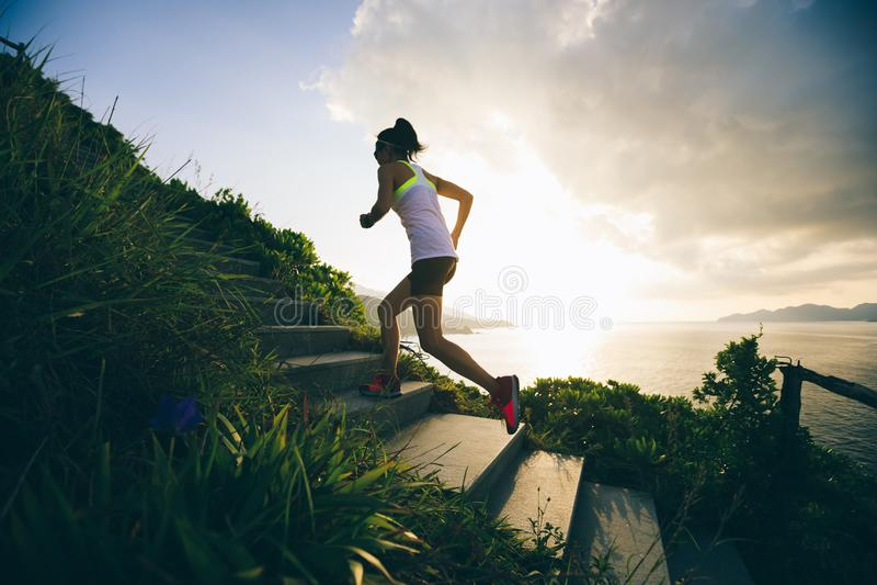 Femme courant sur des escaliers de montagne de bord de la mer photos libres de droits