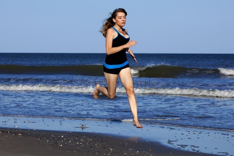 Femme courant sur la plage nu-pieds images stock