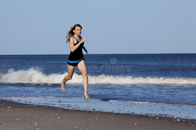Femme courant sur la plage nu-pieds image libre de droits