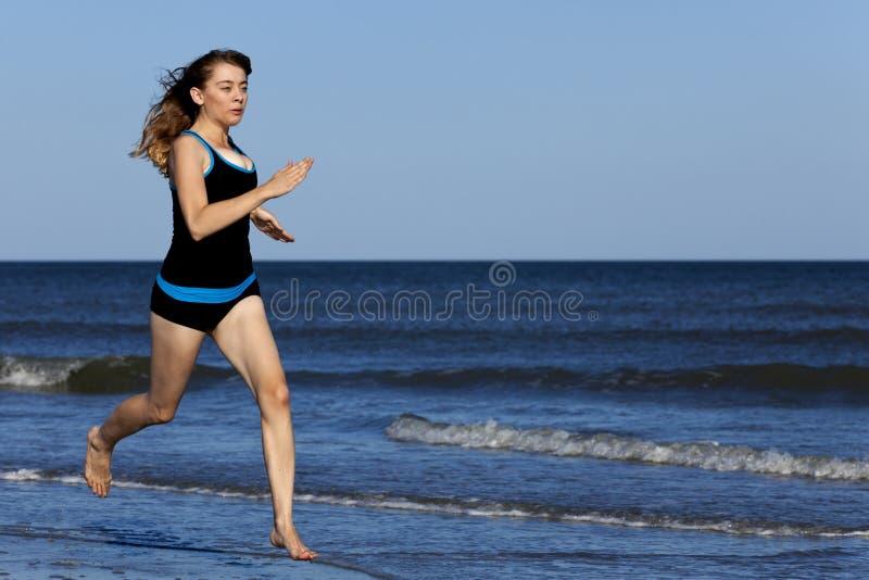 Femme courant sur la plage nu-pieds photo stock