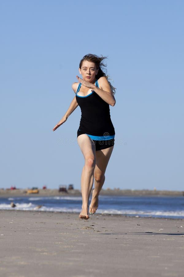Femme courant sur la plage nu-pieds image stock