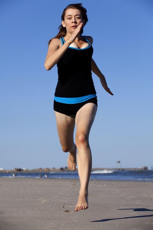 Femme courant sur la plage nu-pieds photo libre de droits