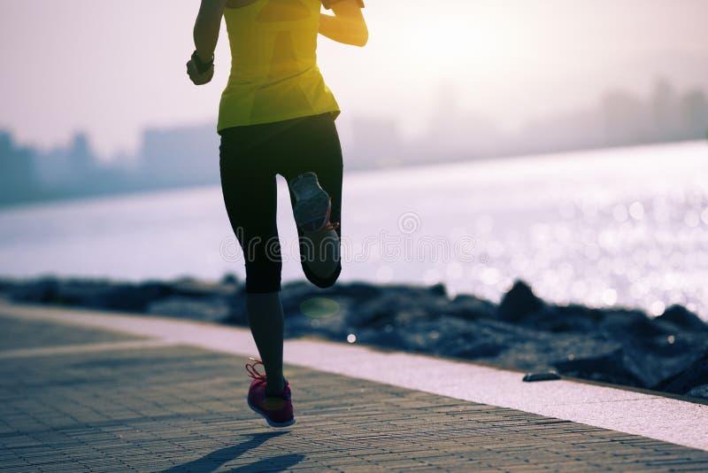 Femme courant sur la traînée de côte de lever de soleil photographie stock libre de droits