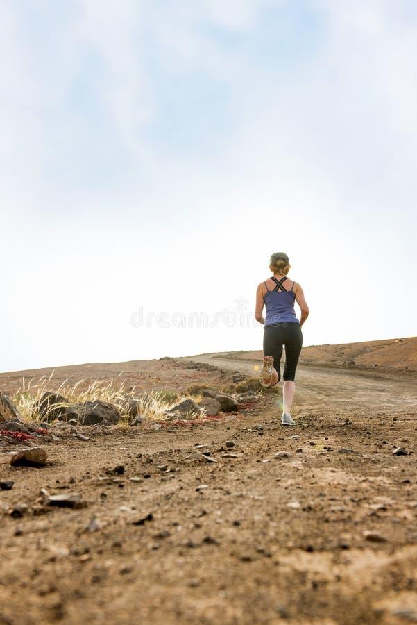 Femme courant sur le chemin de terre pour la forme physique photos stock
