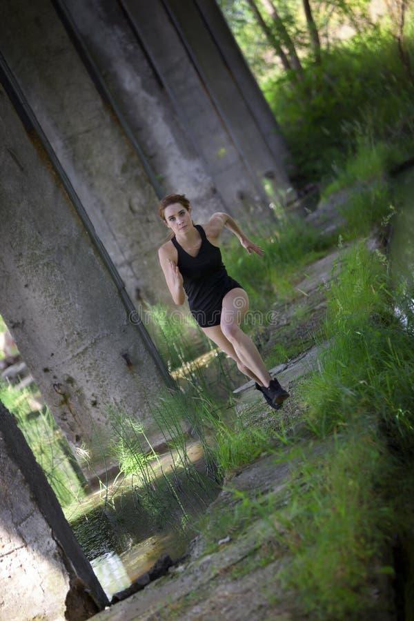 Femme de forme physique courant dans l'environnement post-industriel photo stock