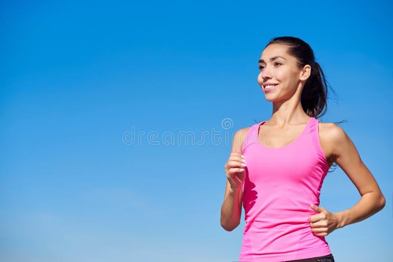 Femme courante de forme physique Femme s'exerçante dans le dessus rose sur un fond bleu photographie stock libre de droits