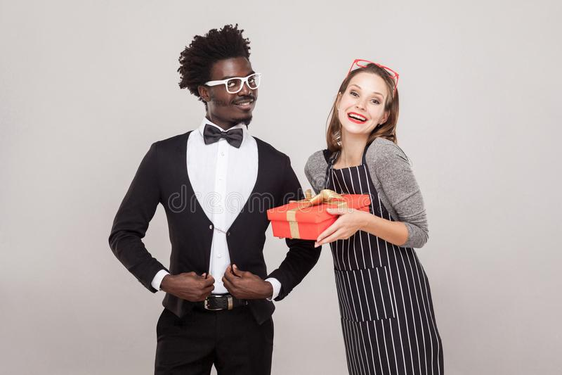 Femme couverte de taches de rousseur tenant le boîte-cadeau, homme africain presque se tenant photographie stock