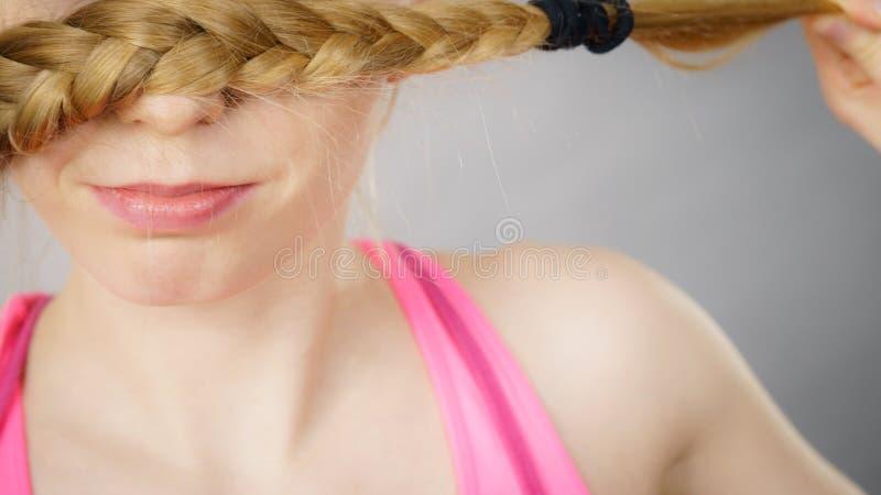 Femme couvrant sa bouche de tresse blonde image stock