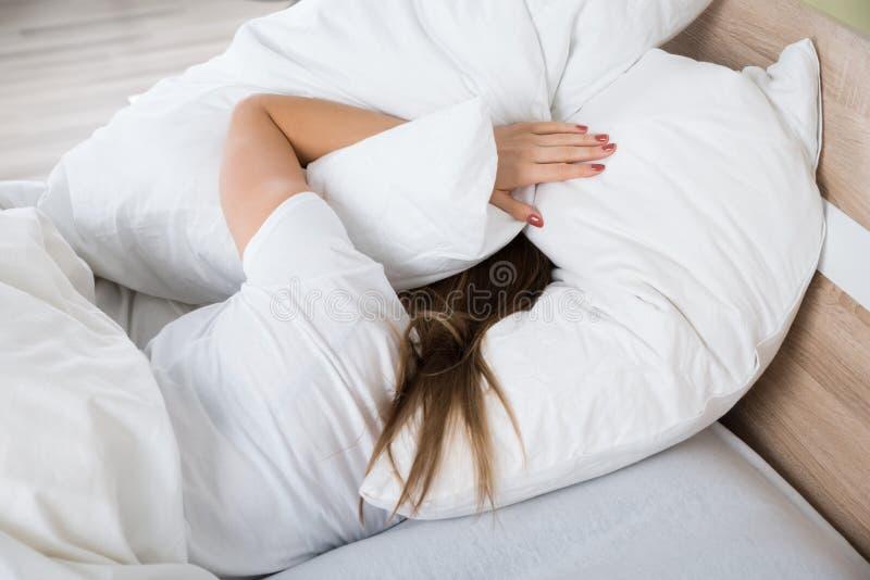 Femme couvrant sa tête d'oreiller photo libre de droits