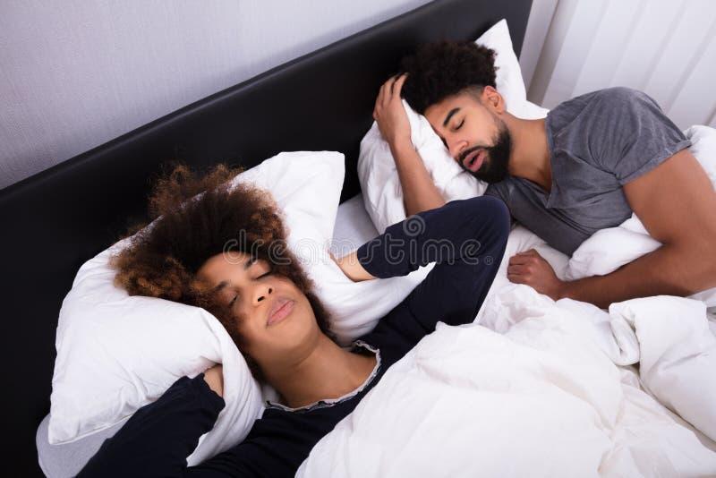 Femme couvrant ses oreilles tandis qu'homme ronflant dans le lit photo libre de droits