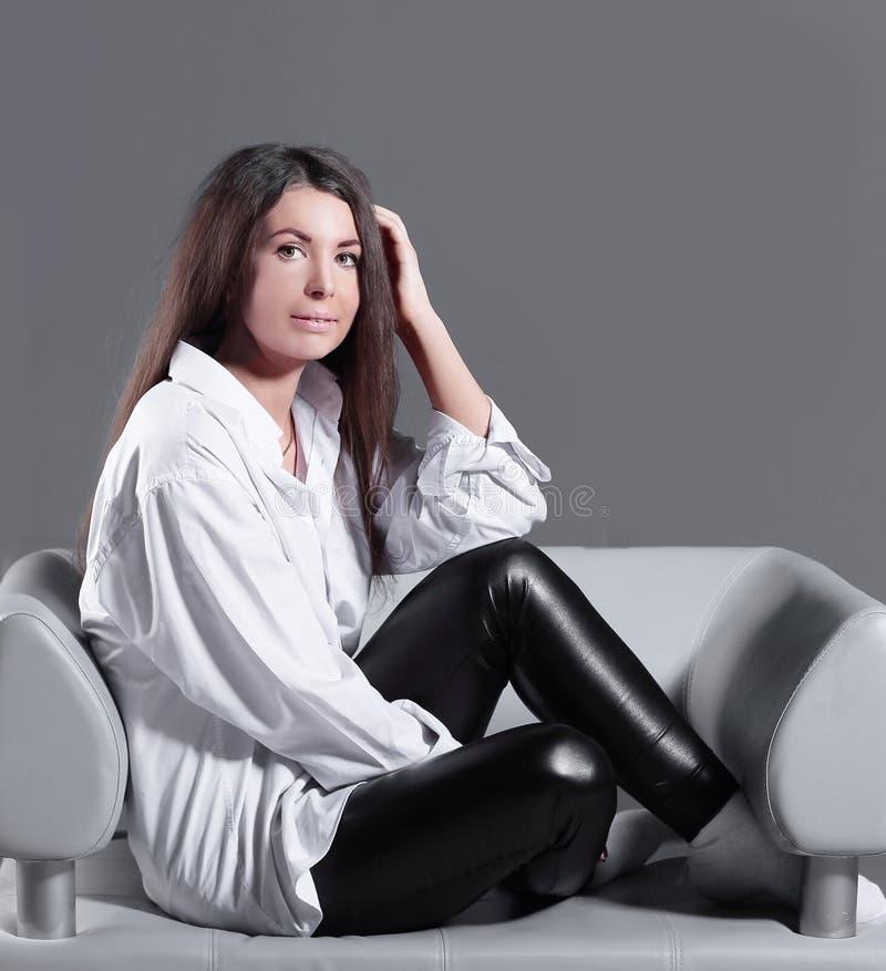 Femme cr?ative d'affaires s'asseyant sur la chaise de bureau sur le fond gris photos stock