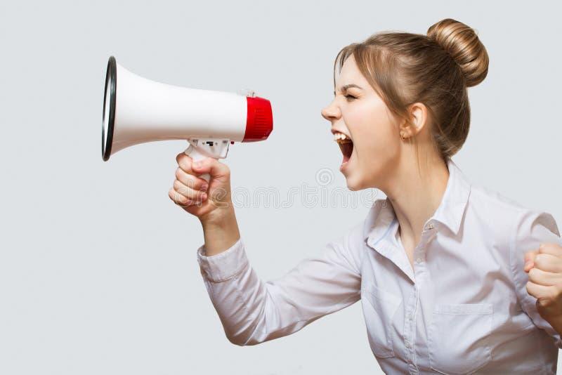 Femme criant dans un mégaphone photographie stock libre de droits