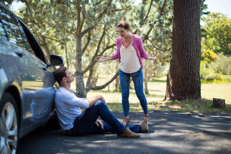 Femme criant sur l'homme s'asseyant en la voiture de panne photos libres de droits