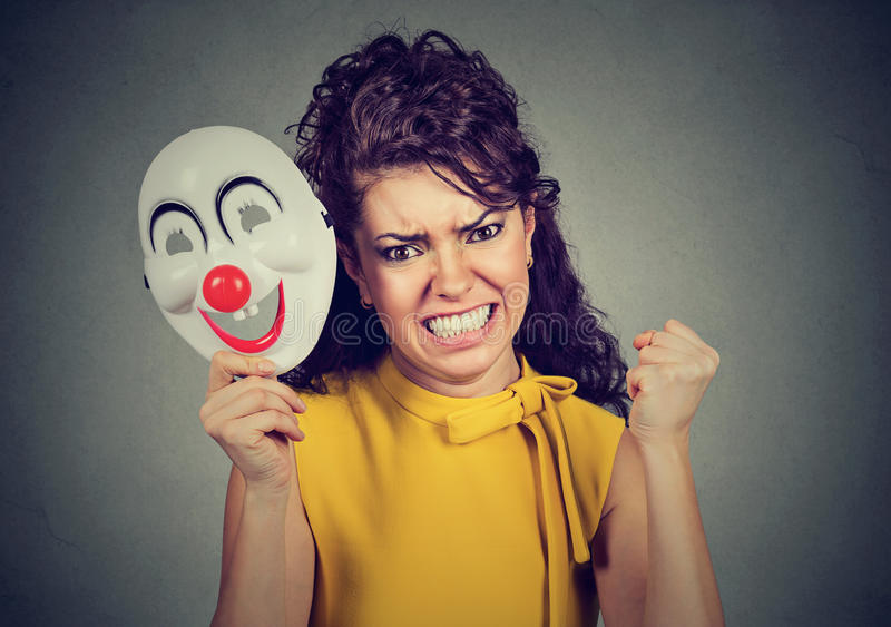 Femme criarde fâchée enlevant le masque de clown exprimant le bonheur photos libres de droits