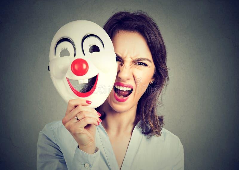 Femme criarde fâchée enlevant le masque heureux de clown image stock