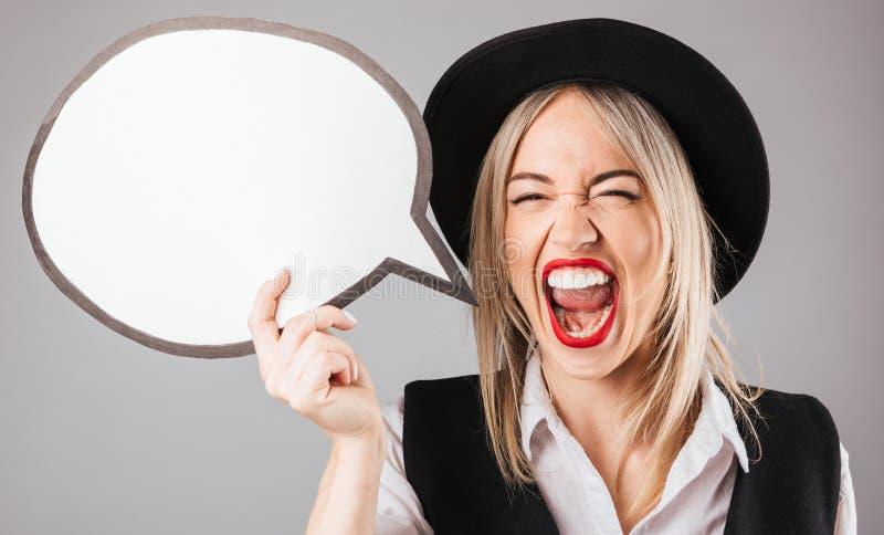 Femme criarde joyeuse enthousiaste dans le chapeau noir et des lèvres rouges jugeant le spech blanc emoty buble photo stock