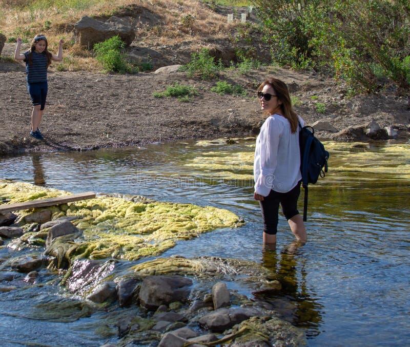 Femme croisant un courant avec la fille jouant en courant ou rivière image stock