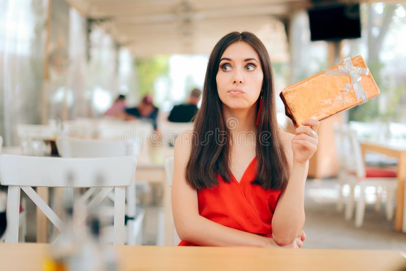 Femme curieuse vérifiant le boîte-cadeau une date photo stock