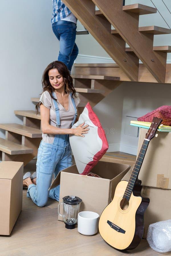 Femme déballant le coussin de la boîte en carton images libres de droits