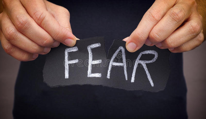 Femme déchirant le mot de crainte écrit sur le papier noir image libre de droits