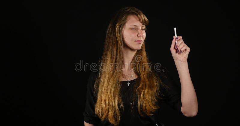 Femme décidant entre la cigarette électronique ou normale sur le fond noir image stock