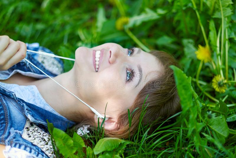Femme décontractée écoutant la musique avec des écouteurs se trouvant sur l'herbe images stock
