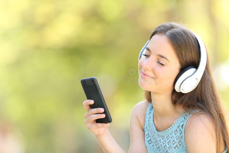 Femme décontractée écoutant la musique avec les yeux fermés image libre de droits