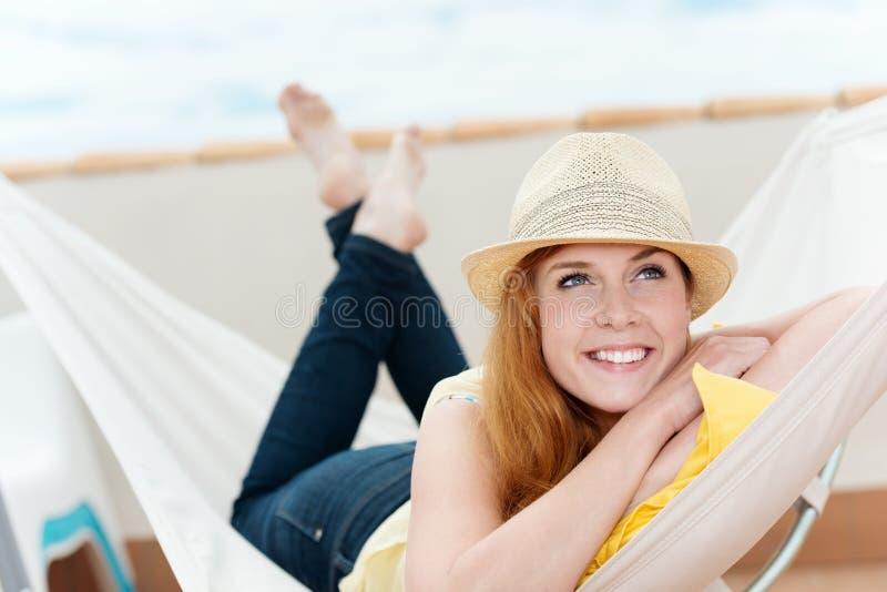 Femme décontractée heureuse rêvassant dans l'hamac photos stock