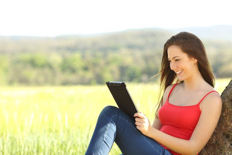 Femme décontractée lisant un ebook dans le pays image stock