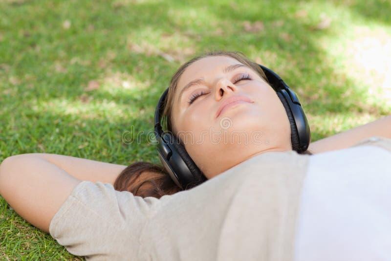 Femme décontractée se trouvant sur la pelouse appréciant la musique images stock
