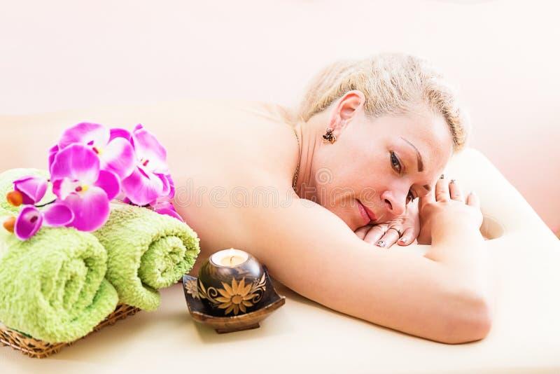 Femme décontractée sur la table de massage recevant le traitement de beauté à la station thermale de jour images libres de droits