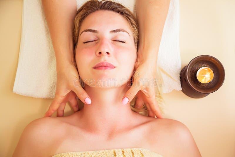 Femme décontractée sur la table de massage recevant le traitement de beauté à la station thermale de jour photographie stock