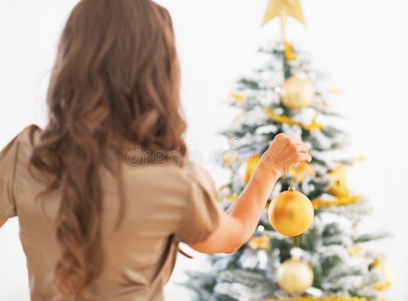 Femme décorant l'arbre de Noël. vue arrière photos stock