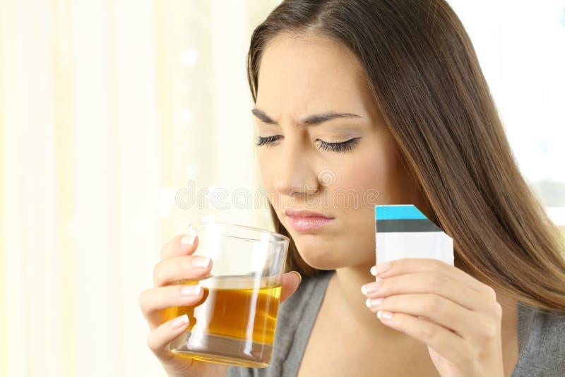 Femme dégoûtée prenant une médecine avec le mauvais goût photo stock
