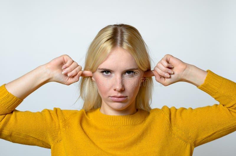 Femme dégoûtée couvrant ses oreilles de doigts images libres de droits
