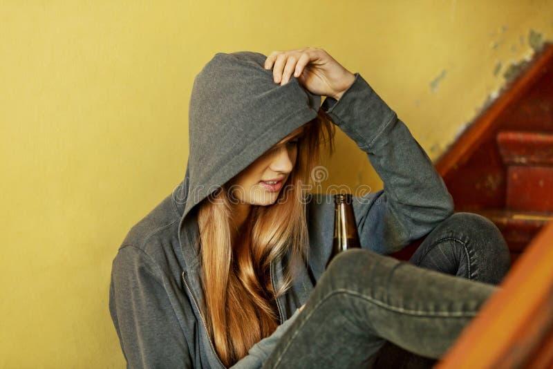 Femme déprimée adolescente s'asseyant sur l'escalier et buvant d'une bière photographie stock libre de droits