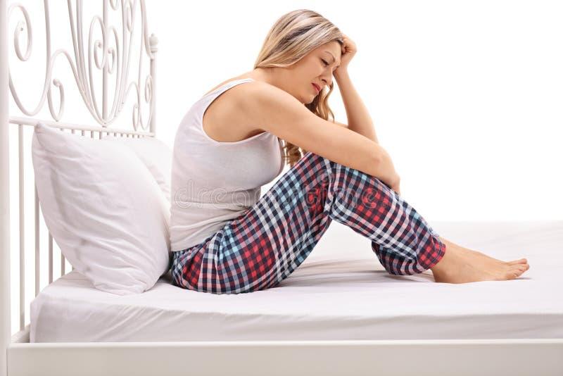 Femme déprimée s'asseyant sur un lit et pleurer photos libres de droits