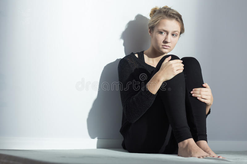 Femme déprimée s'asseyant sur un plancher photographie stock libre de droits