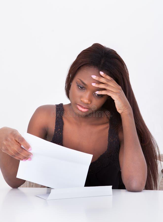 Femme déprimée tenant Bill At Table image stock